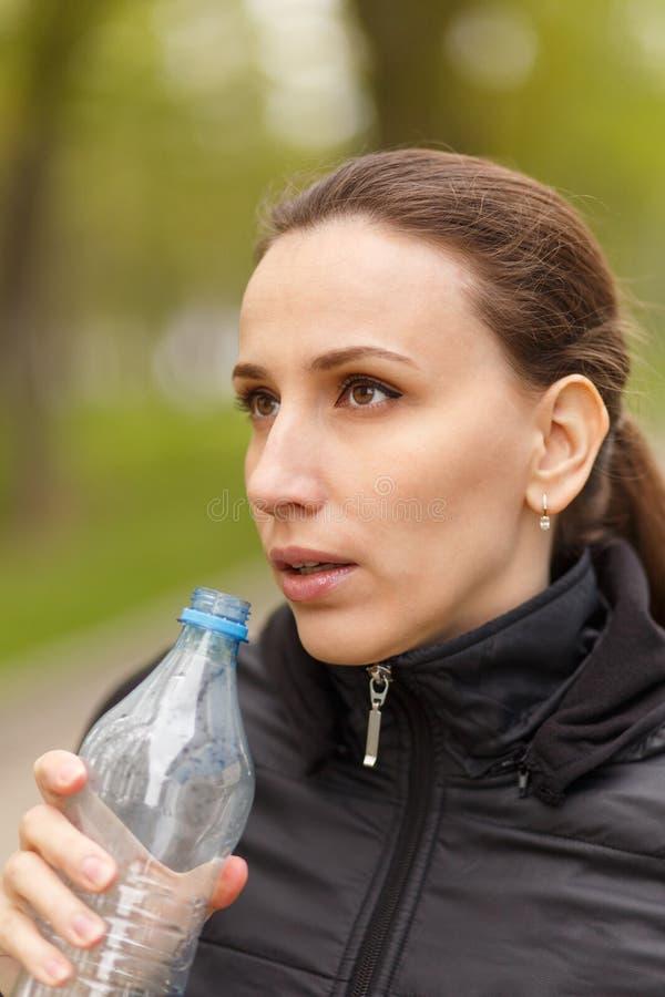 Agua potable de la mujer joven después de activar del entrenamiento foto de archivo