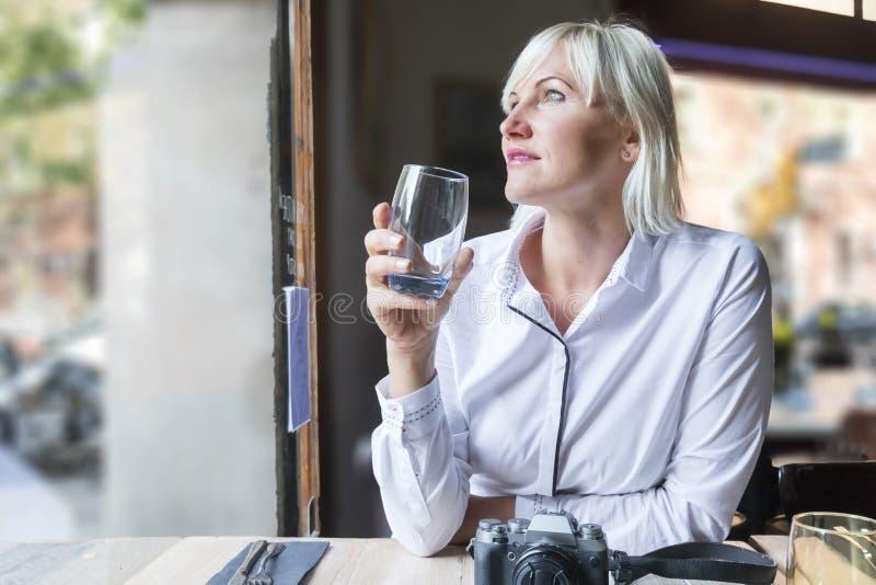 Agua potable de la mujer joven en un café foto de archivo