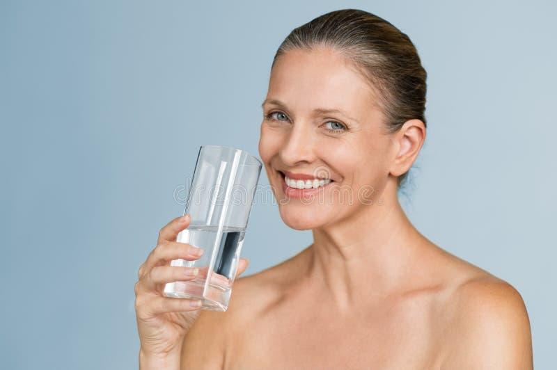 Agua potable de la mujer madura fotografía de archivo