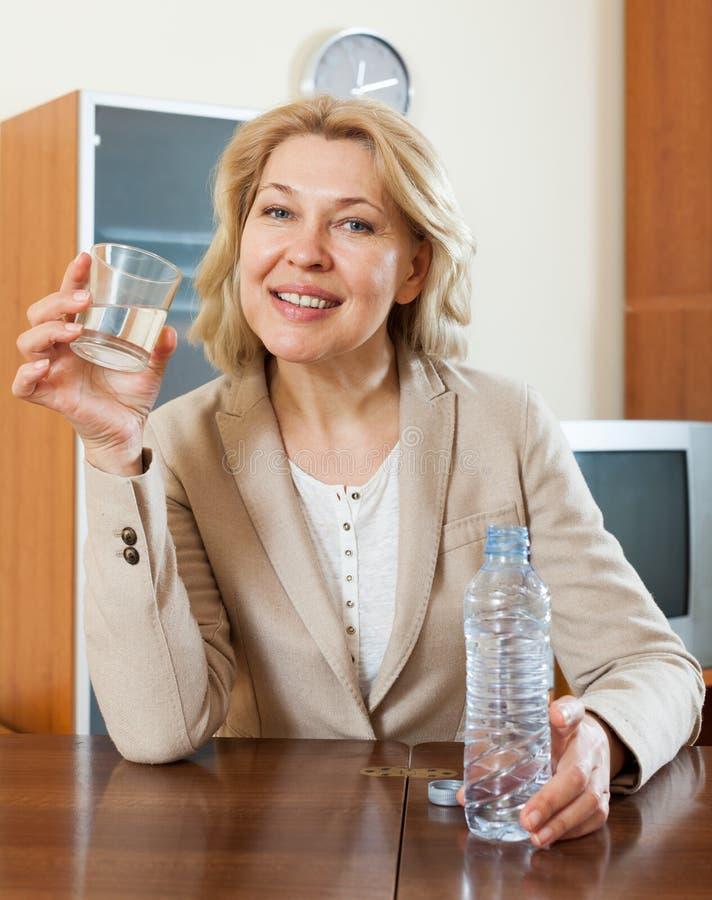 Agua potable de la mujer madura feliz fotos de archivo