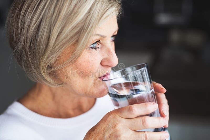 Agua potable de la mujer mayor en la cocina fotos de archivo