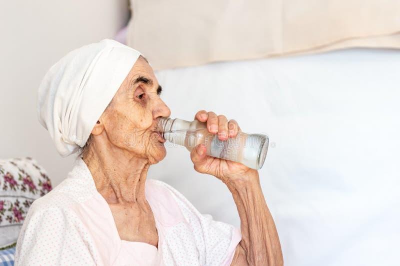 Agua potable de la mujer mayor sedienta de una botella en su sitio fotografía de archivo