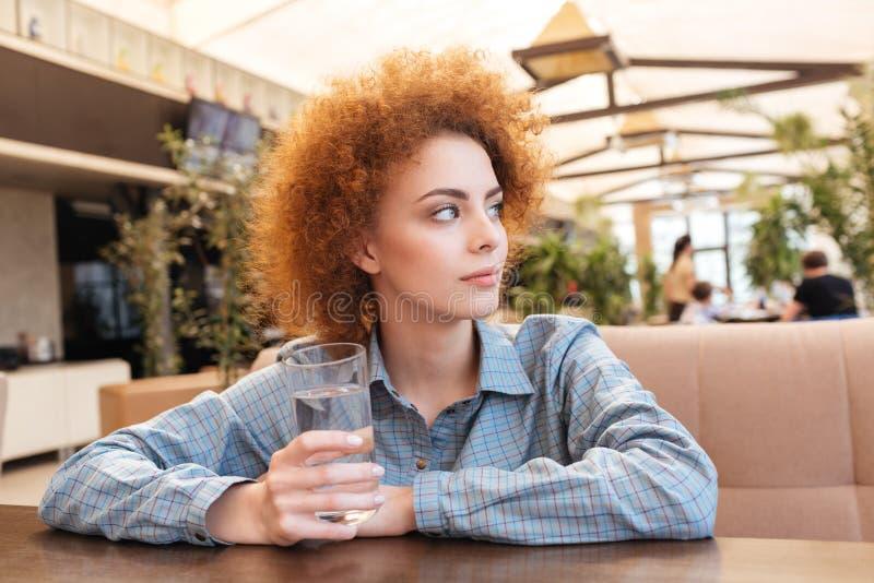 Agua potable de la mujer pensativa en la tabla en café imagen de archivo libre de regalías