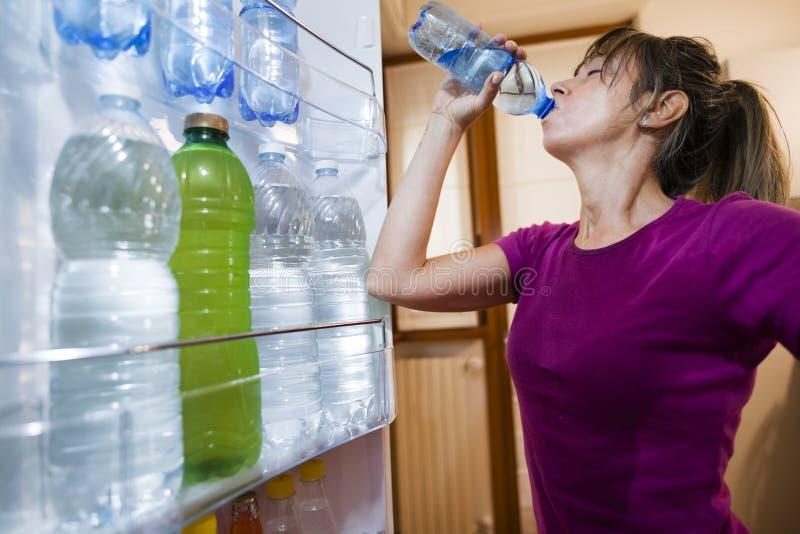 Agua potable de la mujer sudorosa vista por dentro del refrigerador imágenes de archivo libres de regalías
