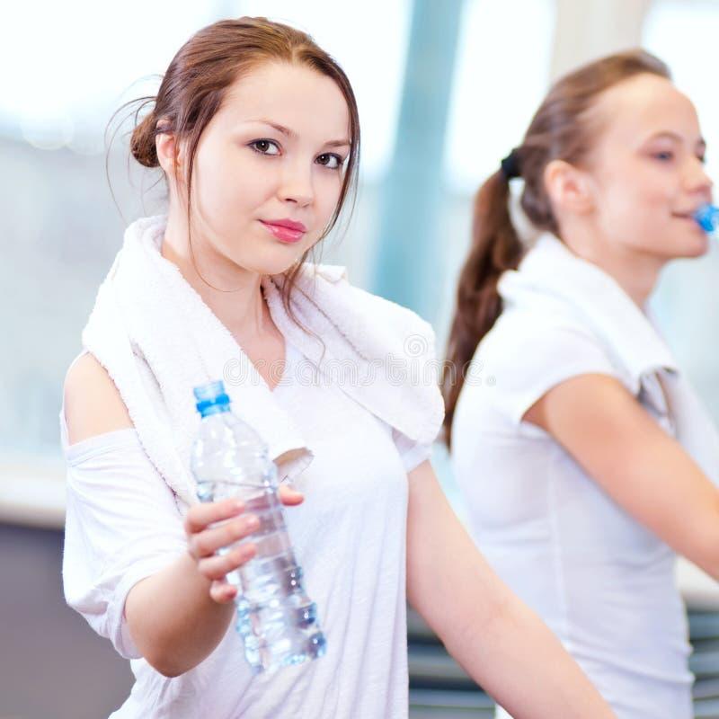 Agua potable de las mujeres después de deportes fotos de archivo