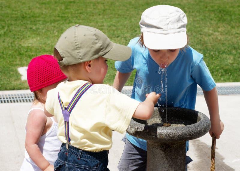 Agua potable de los niños en una fuente de consumición foto de archivo