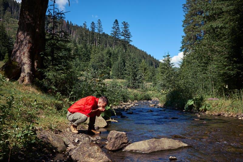 Agua potable del caminante sediento en el río de la montaña fotos de archivo