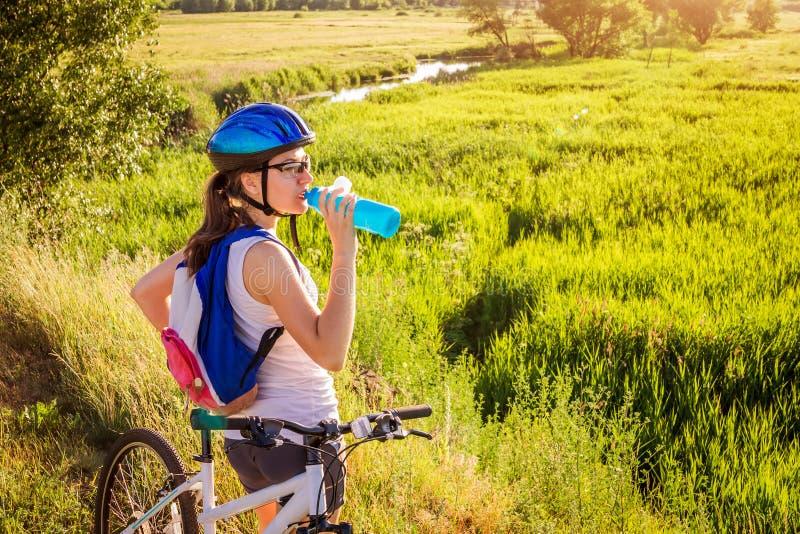 Agua potable del ciclista joven por el río foto de archivo