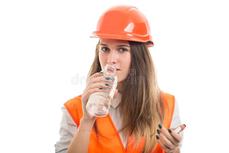 Agua potable del constructor de la mujer joven imagenes de archivo