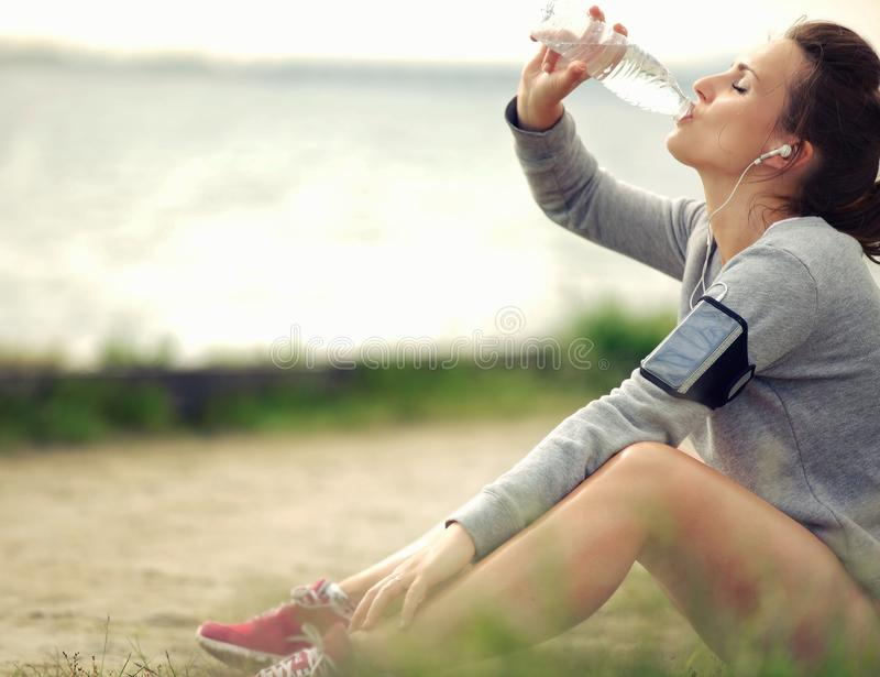 Agua potable del corredor femenino imagen de archivo