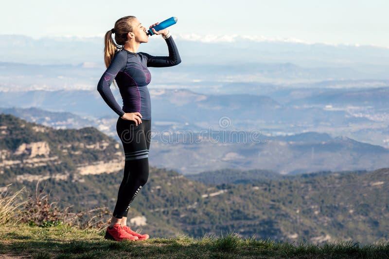 Agua potable del corredor del rastro mientras que mira paisaje del pico de montaña foto de archivo