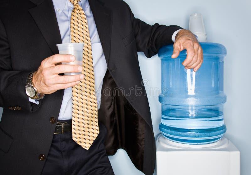 Agua potable del hombre de negocios del refrigerador de agua fotografía de archivo libre de regalías