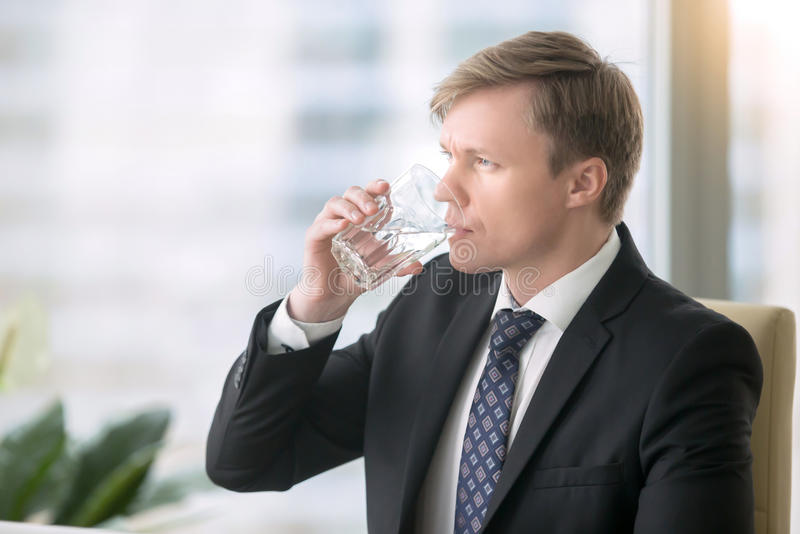 Agua potable del hombre de negocios en el escritorio foto de archivo