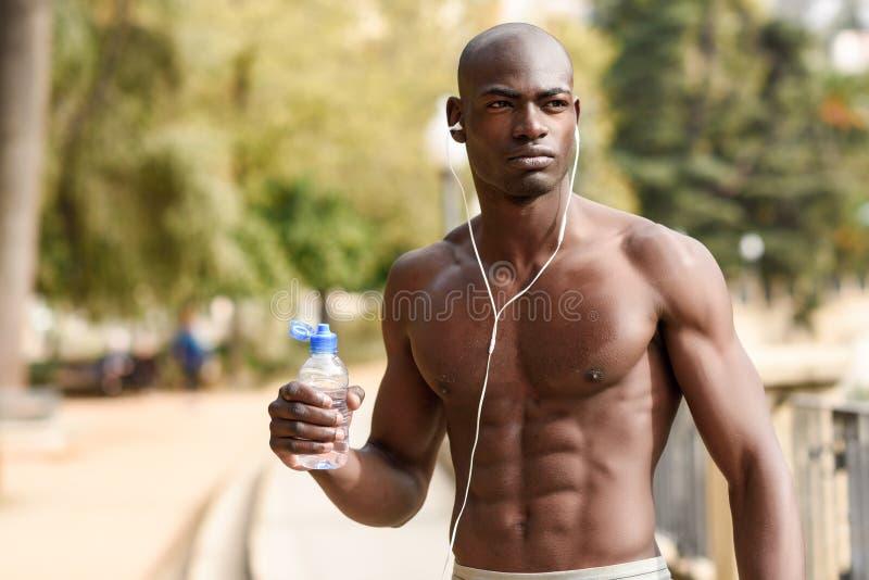 Agua potable del hombre negro después de correr en fondo urbano fotos de archivo libres de regalías