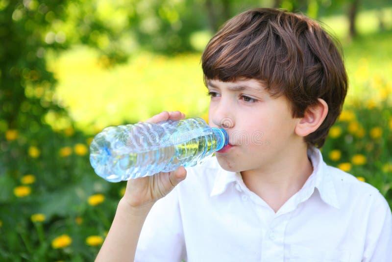 Agua potable del muchacho de la botella al aire libre imagen de archivo libre de regalías