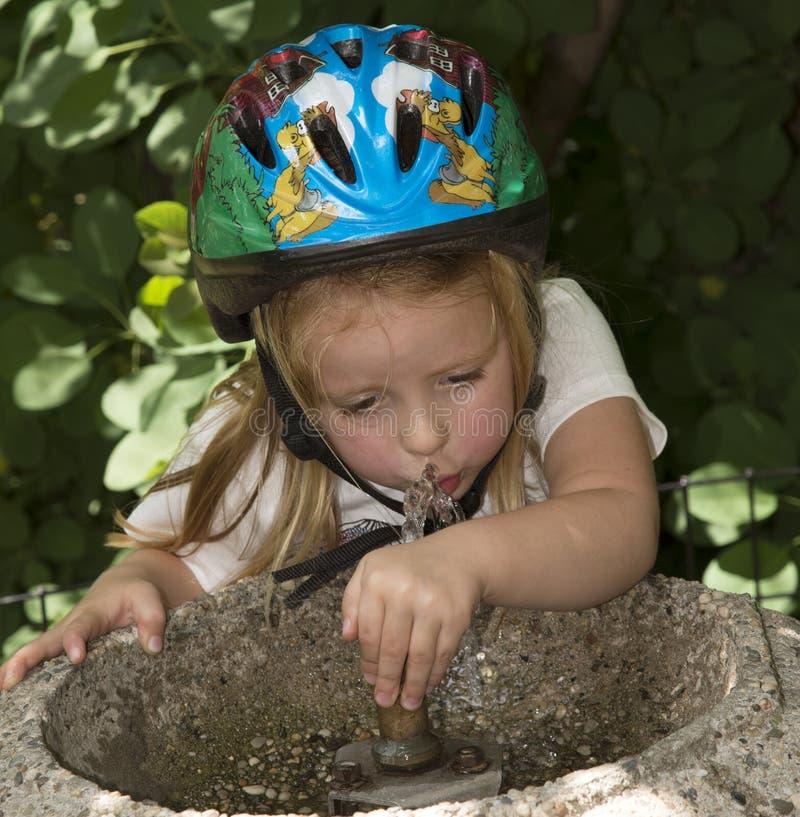 Agua potable del niño de una fuente foto de archivo libre de regalías