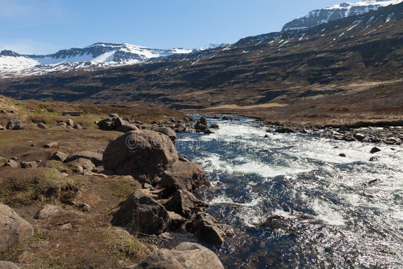 Agua potable del río de la montaña en un paisaje pedregoso de la montaña rocosa de Islandia imágenes de archivo libres de regalías
