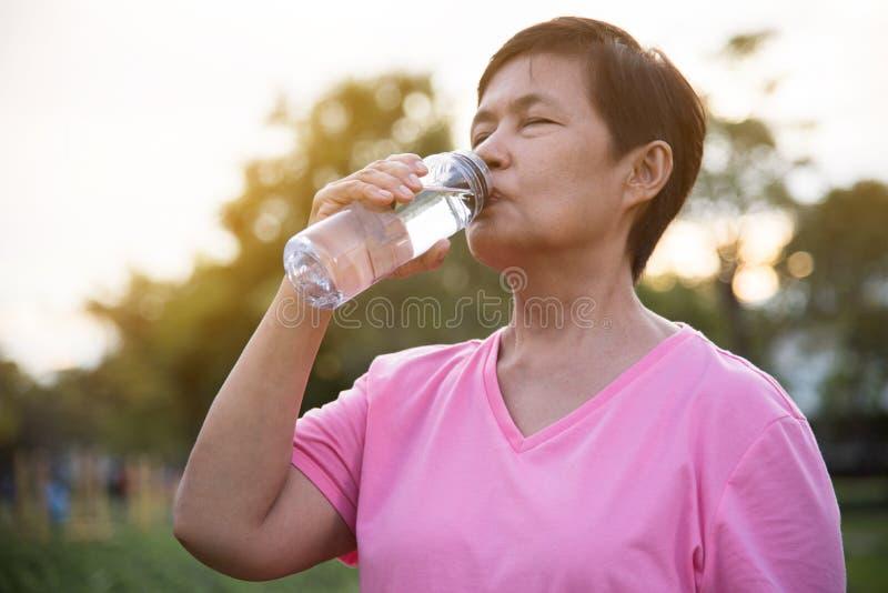 Agua potable femenina mayor asiática fotografía de archivo libre de regalías