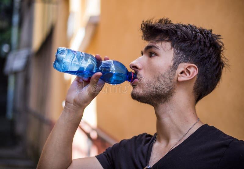 Agua potable hermosa del hombre joven de la botella imagenes de archivo