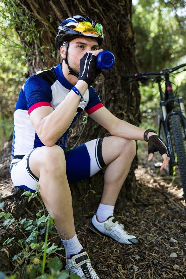 Agua potable hermosa del hombre joven después de completar un ciclo en la montaña fotos de archivo