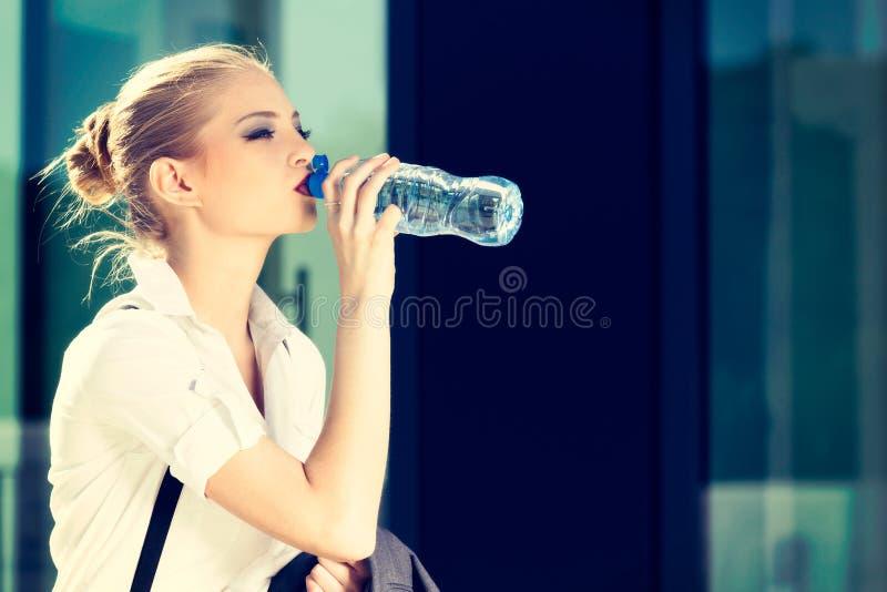 Agua potable joven de la mujer de negocios de una pequeña botella foto de archivo libre de regalías