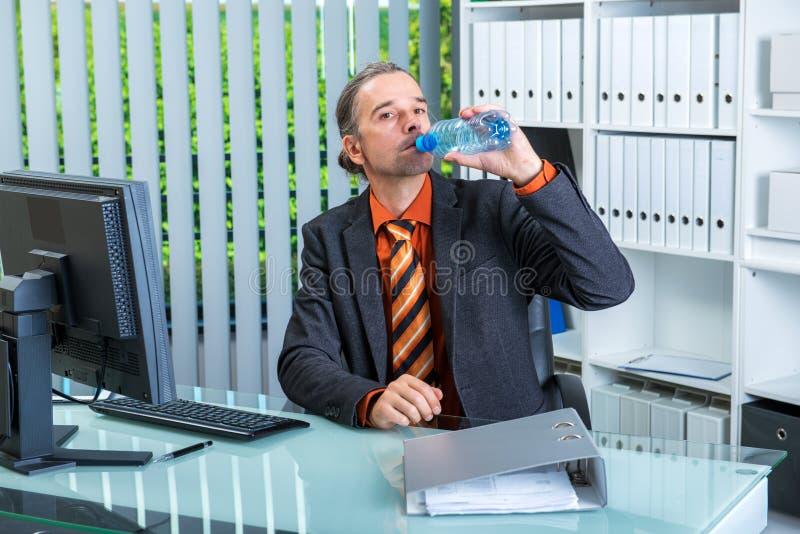 Agua potable joven del hombre de negocios foto de archivo