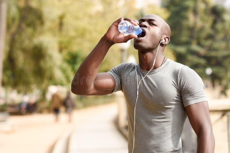 Agua potable joven del hombre negro antes de correr en backgroun urbano imagen de archivo