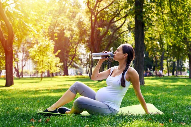 Agua potable juguetona de la mujer embarazada en parque foto de archivo