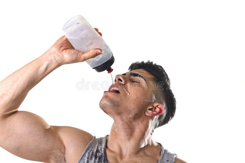 Agua potable sedienta del hombre joven del deporte atlético que lleva a cabo la colada de la botella flúida en cara sudorosa fotos de archivo libres de regalías