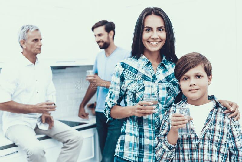 Agua potable sonriente de la familia en vidrios en casa foto de archivo libre de regalías