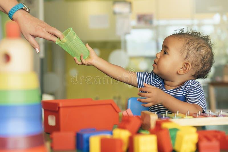 Agua potable y el jugar del bebé feliz imagen de archivo libre de regalías