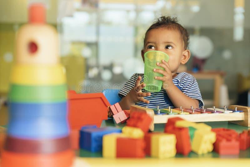 Agua potable y el jugar del bebé feliz fotografía de archivo