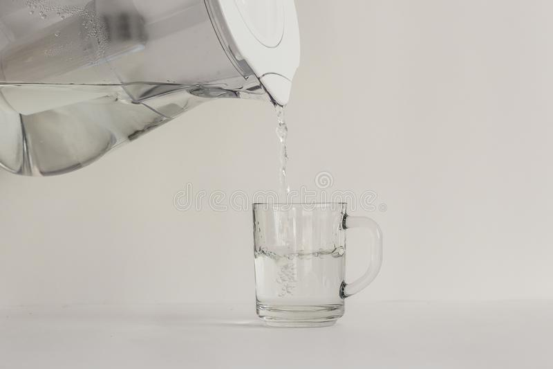 Agua purificada en un jarro con un filtro y un vidrio transparente fotografía de archivo libre de regalías