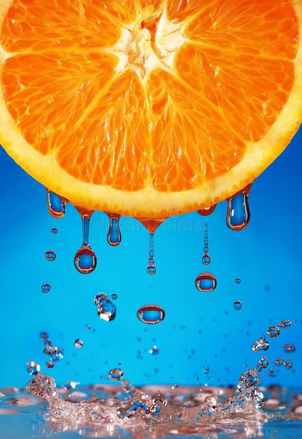 Agua que cae de naranja imagenes de archivo