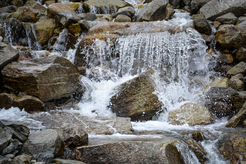 Agua que conecta en cascada sobre rocas imagenes de archivo