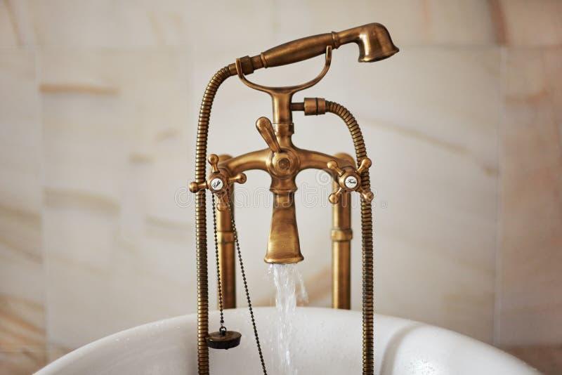 Agua que corre abajo de golpecito de bronce antiguo del grifo en el bathtube foto de archivo