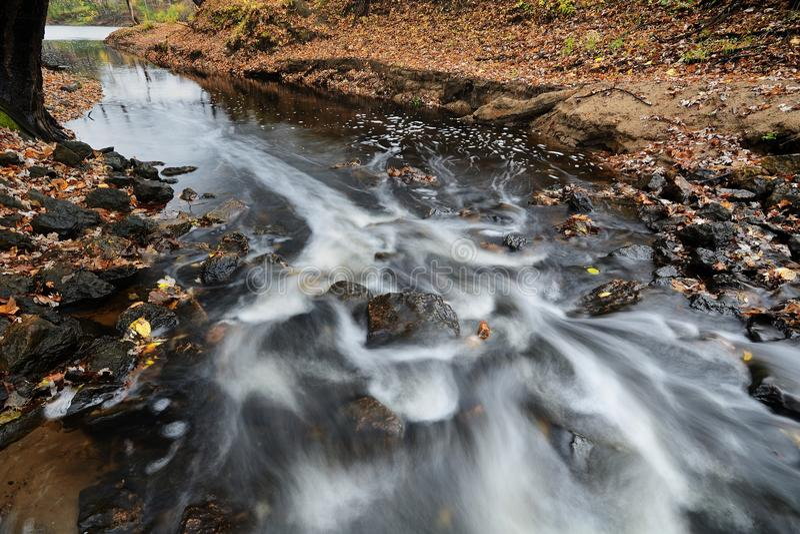 Agua que fluye abajo de los rápidos de una corriente fotos de archivo