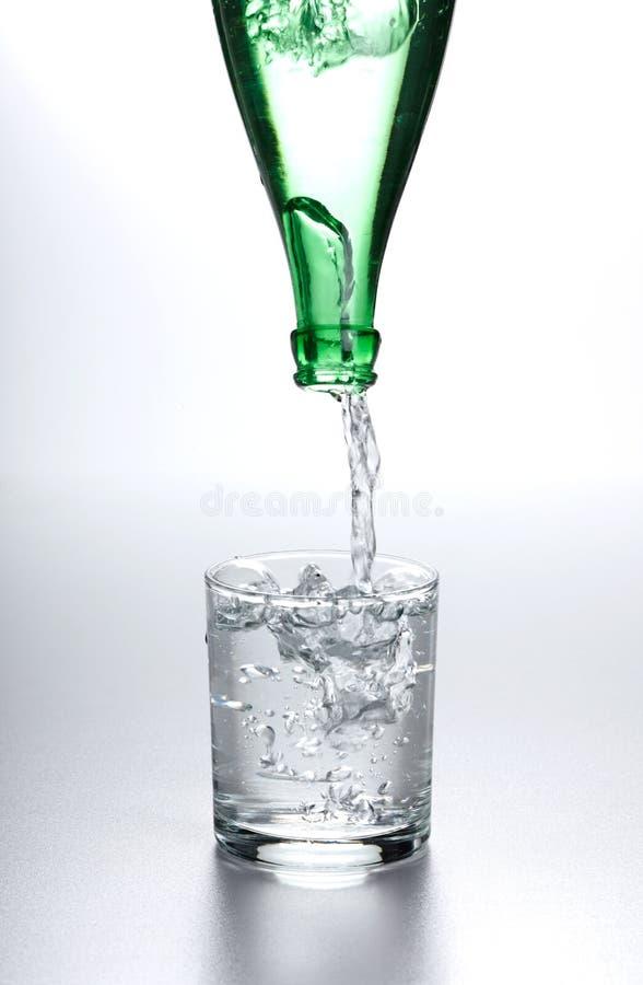 Agua que fluye de la botella en el vidrio imagenes de archivo
