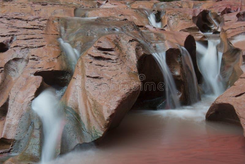 Agua que fluye sobre roca roja imagenes de archivo