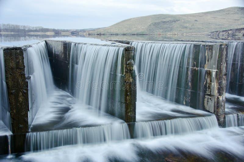 Agua que fluye sobre una presa fotos de archivo libres de regalías