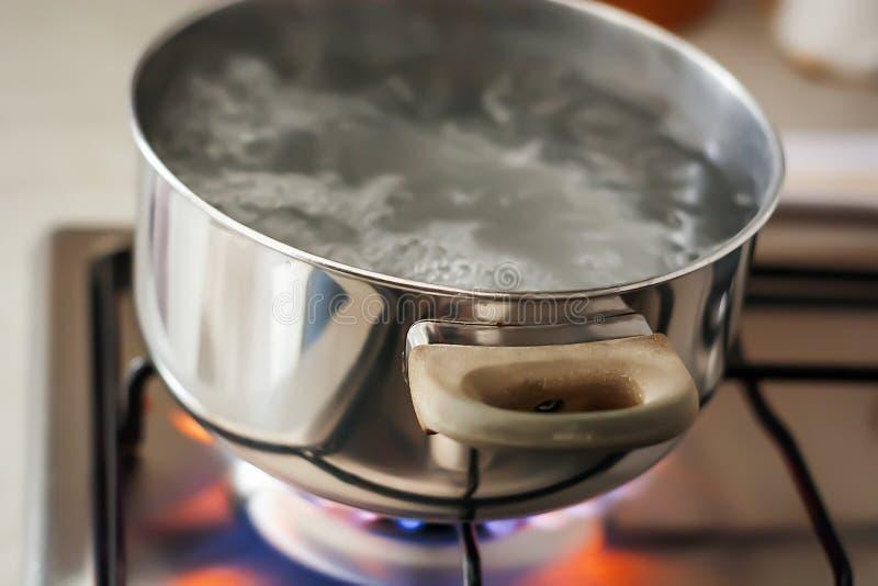 Agua que hierve en un pote sobre una estufa encendida imagen de archivo libre de regalías