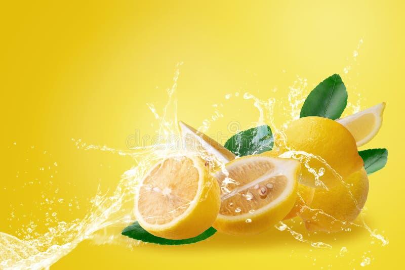 Agua que salpica en la fruta amarilla madura cortada fresca del limón aislada en fondo amarillo imagenes de archivo