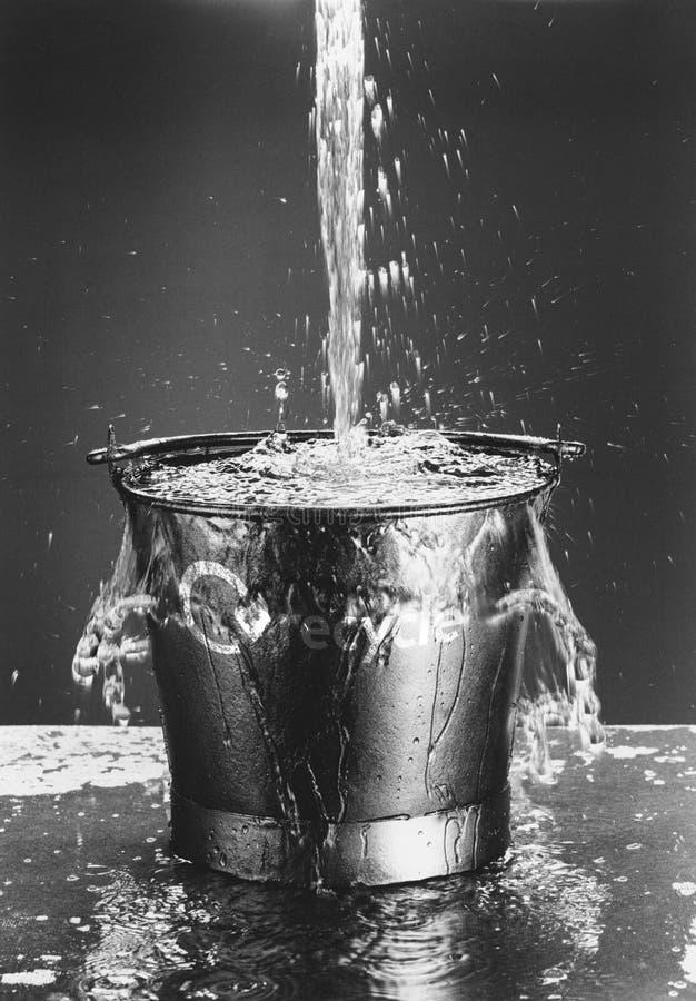 Agua que vierte en cubo imagenes de archivo