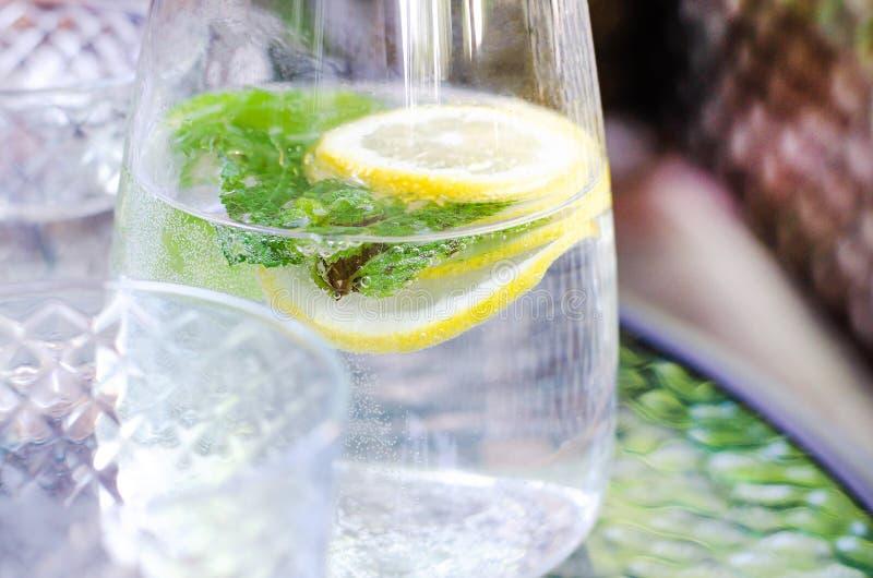 Agua simple con el limón y la menta en un jarro fotografía de archivo