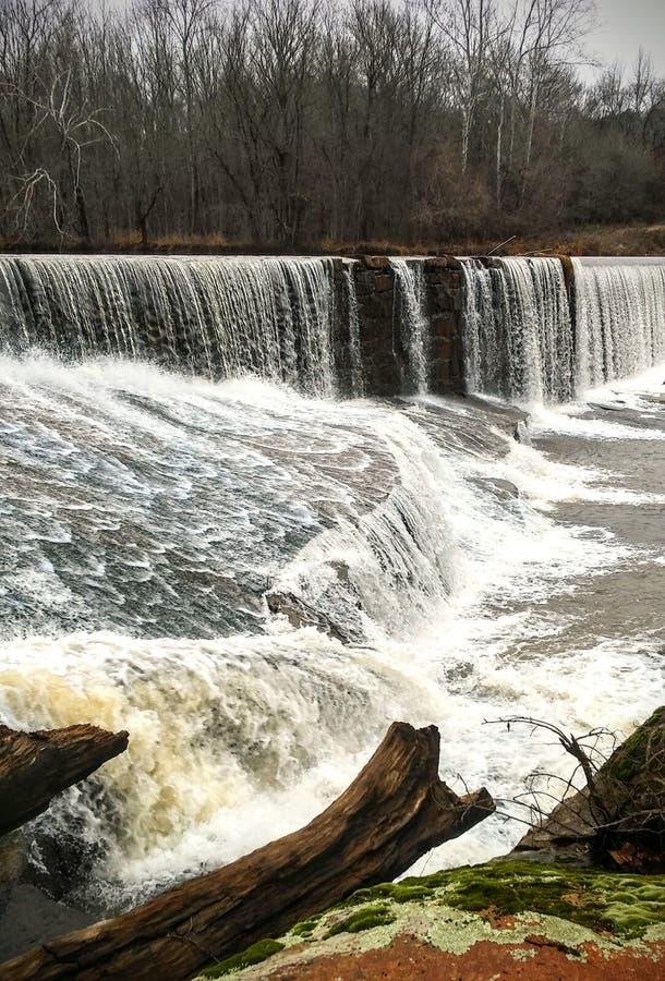 Agua sobre la presa de la roca en invierno imagenes de archivo