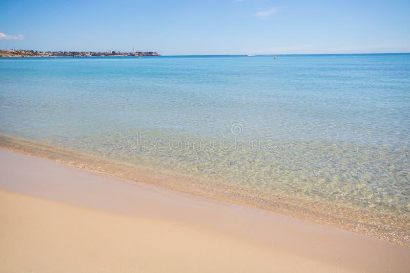 Agua tranquila y clara en una playa arenosa del mar Mediterráneo en un día de verano fotos de archivo libres de regalías