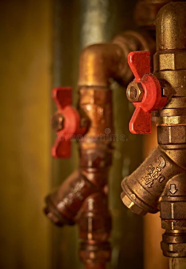 Agua vieja de los tubos de agua, caliente y fría, con las válvulas rojas Orientación vertical Cierre para arriba imágenes de archivo libres de regalías