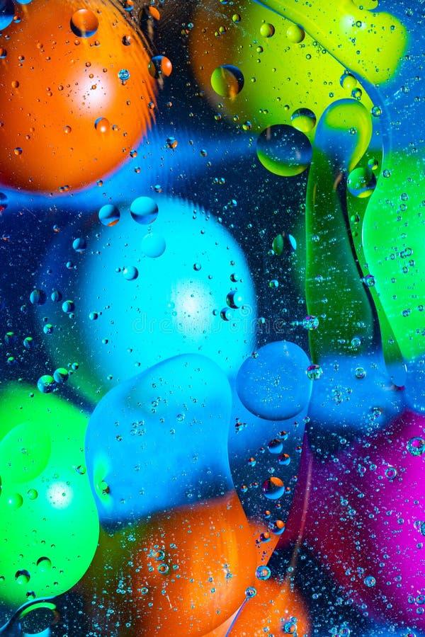 Agua y aceite de mezcla en c?rculos y ?valos abstractos de las bolas del color hermoso de una pendiente del fondo foto de archivo libre de regalías