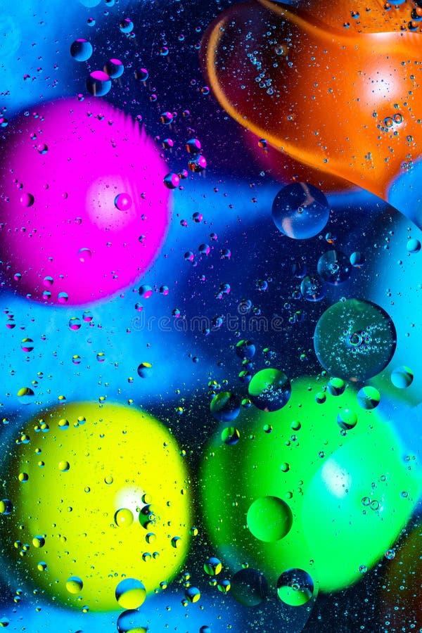 Agua y aceite de mezcla en c?rculos y ?valos abstractos de las bolas del color hermoso de una pendiente del fondo fotografía de archivo