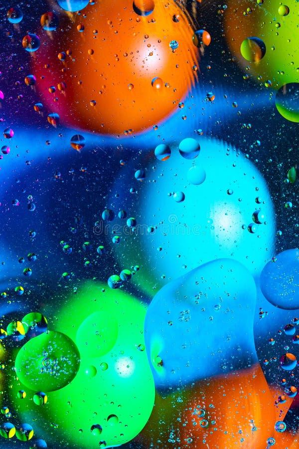Agua y aceite de mezcla en c?rculos y ?valos abstractos de las bolas del color hermoso de una pendiente del fondo fotos de archivo libres de regalías